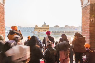 January 2018 - Sunset at The Golden Temple in Amritsar, India. Crowds gather to prey and watch the sunset.