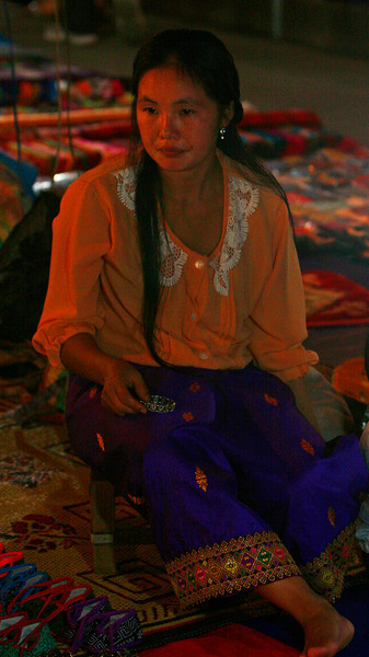 A young mother sells goods in the night market.