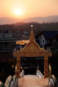 Huay Xai, Laos Looking down from the temple gate at Wat Chomkao Manilat in Huay Xai, Laos as the sun sets across the Mekong River behind the mountains of northern Thailand.