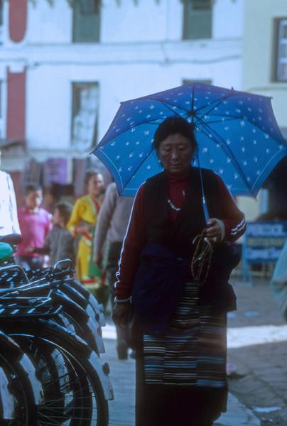 A buddist sherpa woman woman returns from prayers in Bodderum, Nepal