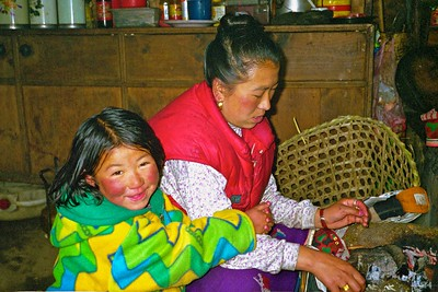 Young sherpa girl practices her alphabet while her mother tends the to the fire and cooking