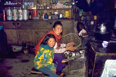 Sherpa woman cooking while singing with her daughter