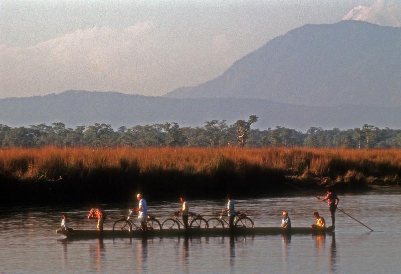 Biking to work. Workers cross Ganadak River in Chitwan, Nepal