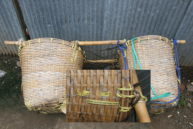 """These koolie baskets were laying next to the bus station in Pai Thailand. the yellow tape used to bind them together is stamped """"seven eleven distribution""""."""