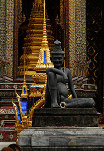 Bangkok, Thailand Bronze statue of a seated hermit (a physician) at the entrance to Wat Phra Kaew (Temple of the Emerald Buddha) in Bangkok. This temple is located within the grounds of the Grand Palace, and is considered to be the most sacred temple in all of Thailand.