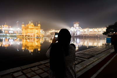 January 2018 - The Golden Temple in Amritsar, India. An Indian lady takes a smartphone picture of the Golden Temple at night.