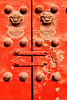 A detail from a pair of doors entering the Forbidden Palace in Beijing. The bronze lions on the bright red paint are guarding the doorway.