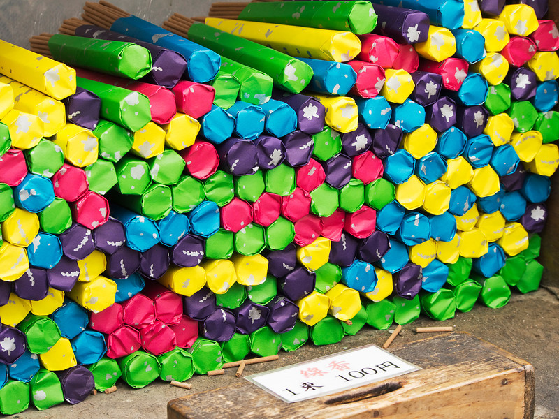 Bundles of incense sticks covered in brightly colored paper are for sale at a Shinto shrine in Tokyo are for sale for 100 Japanese yen.