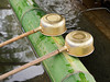 Two brass purification ladles rest on a bamboo log at a Shinto shrine in Japan. The ladles are used as part of the ritual temizu cleansing by worshippers prior to going into the temple.