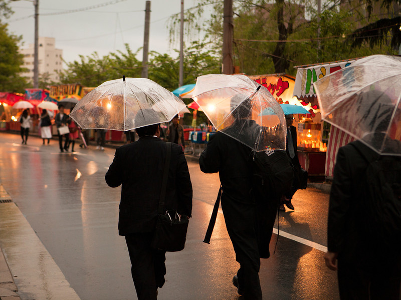 An ordinary street scene of three men walking in the rain with clear umbrellas in Osaka, Japan through a street of shops during the spring cherry blossom festival.