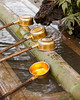 Four metallic ladles full of water are waiting to be used to purify worshippers' hands near a Shinto shrine in Tokyo.