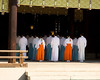 A group of priests are lined up into five rows of five people each, receding into the shadow of the inner sanctuary of the temple. This was viewed at a traditional Shinto temple in Japan.