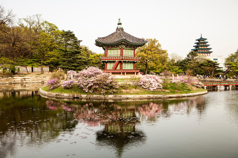 The Pavilion of Far-Reaching Fragrance sits on an artificial island in the Gyeongbokgung Palace complex in Seoul, Korea. The island can only be reached via a bridge that is visible at the right.