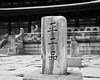 A stone pedestal with an inscription is located in a courtyard in front of one of the larger buildings in the Gyeongbok palace complex in Seoul, Korea. (Scanned from black and white film.)
