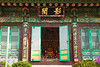 One of the smaller buildings at the Bongeunsa Buddhist temple in Seoul, South Korea. The figure of the Buddha is visible in all his splendor through the entrance door