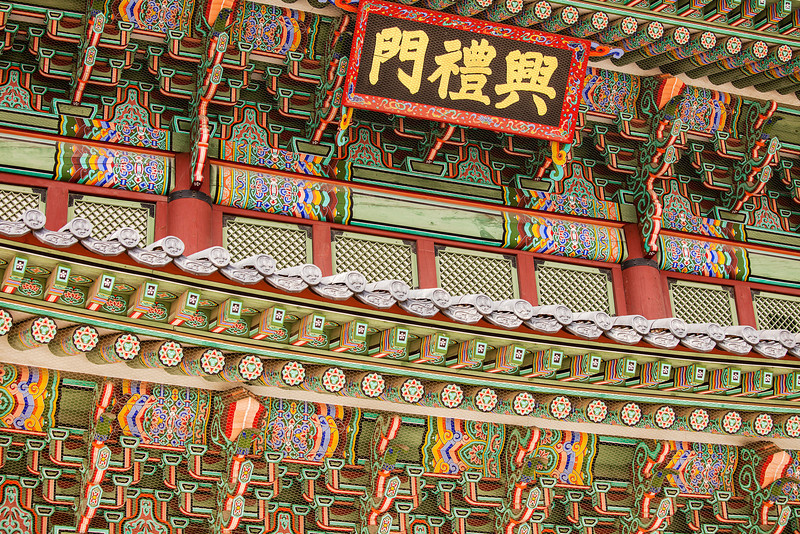 The facade of the Heungnyemun Gate (or Second Gate) of the royal Gyeongbokgung Palace complex in Seoul is built with intricate wooden beams and is decorated with bright paints.