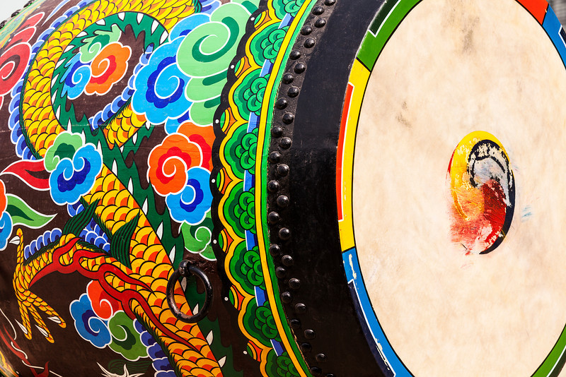 A detailed view of the ornamental paint patterns on a ceremonial drum seen in the Gyeongbokgung Palace complex. The drumhead skin shows the blurred marks made when it is struck.