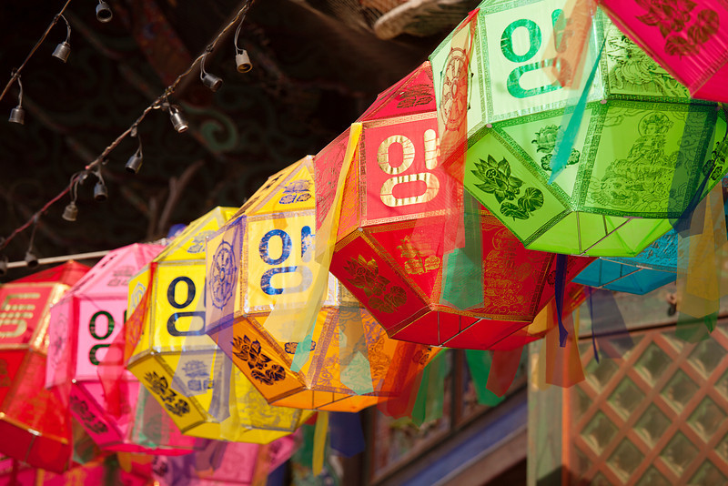 A string of colored paper lanterns hang over the outside entrance to the Buddhist temple of Bongeunsa in Seoul, South Korea.