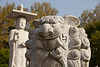 A lion carved out of white marble stands in front of a large, imposing figure of Buddha at an outdoors worship area in the Bongeunsa temple in Seoul, South Korea.