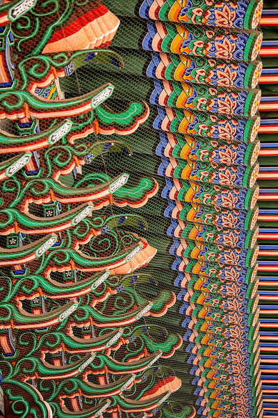 The roof beams over a covered walkway at the Gyeongbokgung Palace complex form a pattern of bright colors and forms.