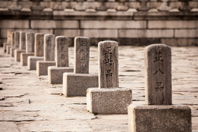 A row of Korean rank stones, or pumgyeseoks, in the main courtyard of the royal Gyeongbokgung Palace complex. Before an audience with the king, nobles would line up according to their ranks as indicated on the stone pillars.