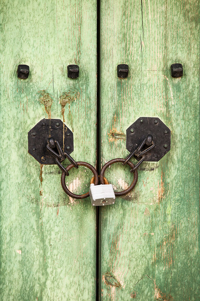 A close-up view of the hardware on an antique Korean door in the Gyeongbokgung Palace complex with a contrast between old iron hardware and a modern padlock.