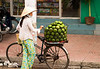 A woman street vendor selling large green fruit on the streets of Ho Chi Minh City in Vietnam.