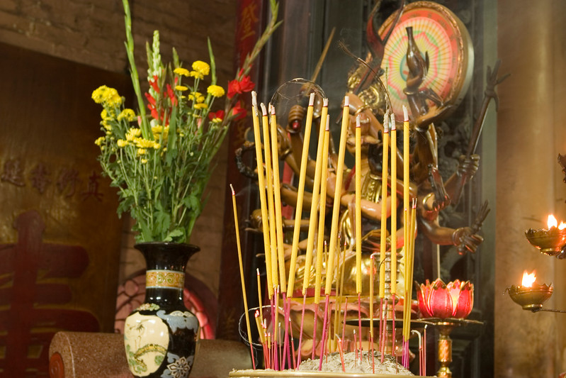 An altar in a Buddhist temple in Vietnam. In the foreground, an urn is filled with burning incense sticks giving off smoke. A flower urn provides some color while a statue with many arms in the background completes the image.