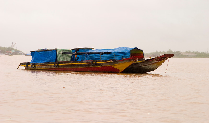 Two river boats at anchor in the Mekong River delta in Vietnam that are fully loaded with cargo and covered with blue tarps.
