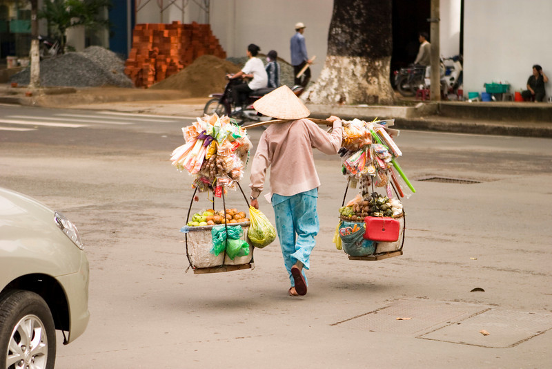 A Vietnamese street vendor in Ho Chi Minh City (Saigon) carrying their goods across a street.
