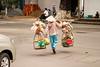 A Vietnamese street vendor in Ho Chi Minh City (Saigon) carrying their goods across a street.