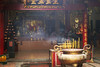 The interior of a Buddhist temple in Vietnam. In the foreground, a ceremonial urn is filled with sticks of burning incense that are filling the air with smoke. In the background, one of the altars is barely visible through the smoke.
