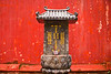 A temple marker with Chinese characters showing in contrast against a red wall.