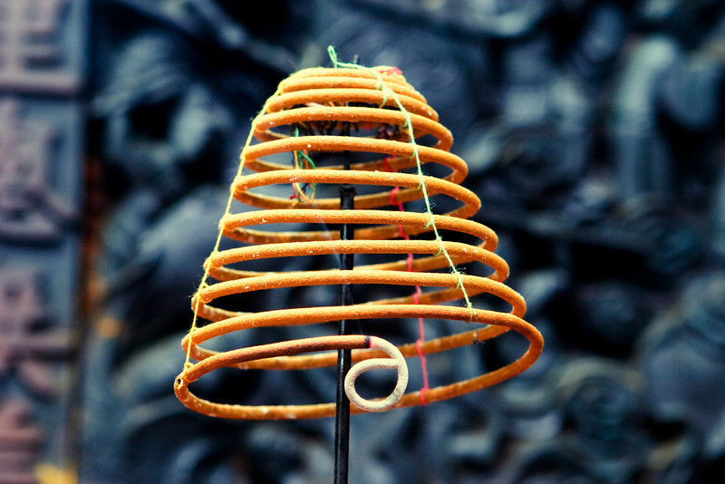 A coil of smoking incense in a Buddhist temple in Vietnam. The tip of the coil with the ash has curled around. This incense coil, held together loosely with colored thread, is located in front of an antique carved wooden panel.