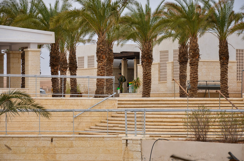 An Israeli soldier stands guard at the visitor's center across the river.