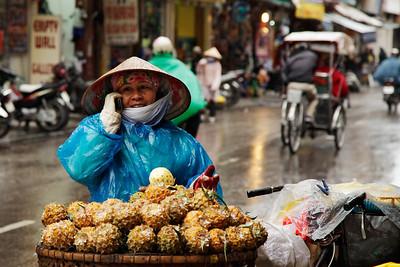 Hanoi, Vietnam A pineapple vendor talks on her cell phone in the Old Quarter, Hanoi.