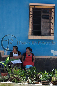 A couple of ladies taking a break from work with a batch of orchids in the foreground. Orchids are everywhere in El Salvador! Concepcion de Ataco, Ahuachapan, El Salvador.