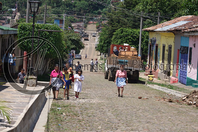 A typical street scene in the village. Notice the woman center frame with the tub on her head. What the women do is they use a yagual, which is a piece of cloth coiled to form a circle, to allow them to balance the tub. This is no easy feat! Concepcion de Ataco, Ahuachapan, El Salvador.