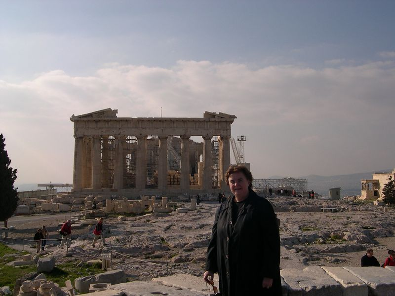 Susan, with the Parthenon in the background.  On the right, you can see the Porch of the Caryatids, with copies of the famous statues of women used a columns.  The original statues are located in the Acropolis museum.