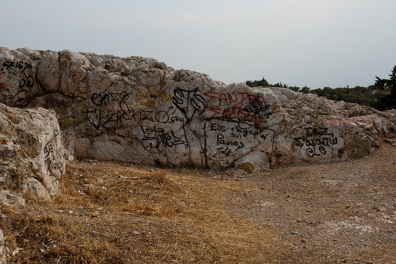 4M9F4920-21 Areopagus Hill or Hill of Ares, located just above the Ancient Agora, is composed of bare marble and provides a wonderful view of the city.  Historically, it is popular with tourists for its connections with a speech made by Paul the Apostle. Here a portion of the hill is shown with graffiti.  The site was at one time a homicide court and once a meeting place for the city elders.