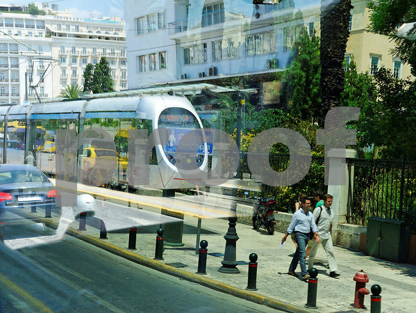 Street scene Athens, Greece. Multiple transportation modes reflection: Car, Motorcycle, Pedestrians, Taxi, Train