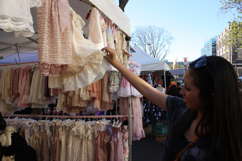 Grace looking at the baby clothes at the market.