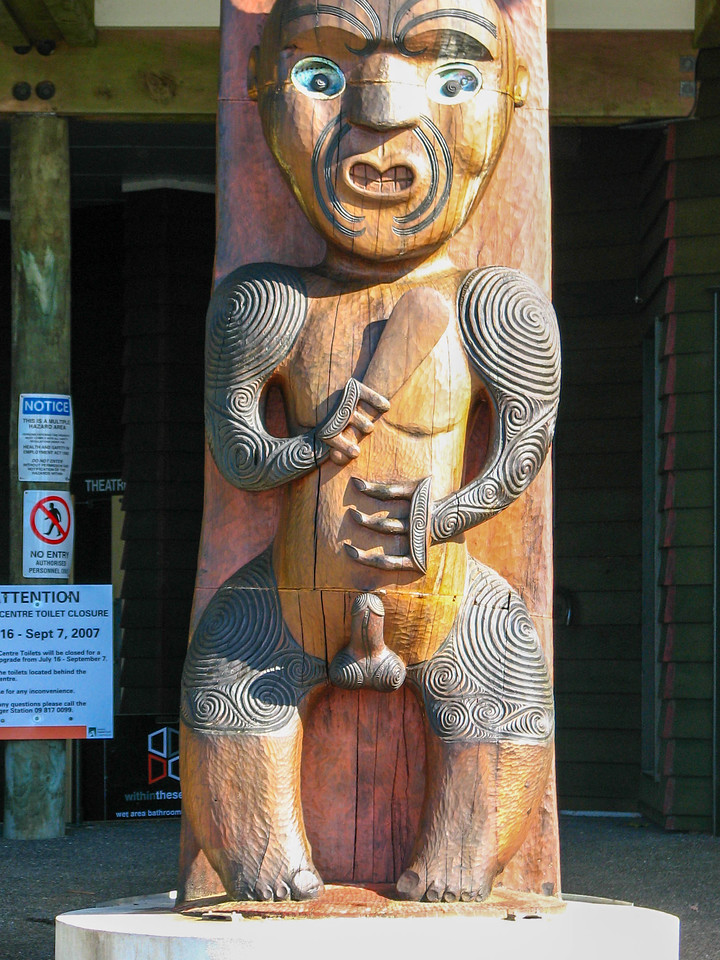 Closeup of the Maori pole outside the Arataki Visitor Centre. Large endowments on these carvings were meant to symbolize the tribe's strength.