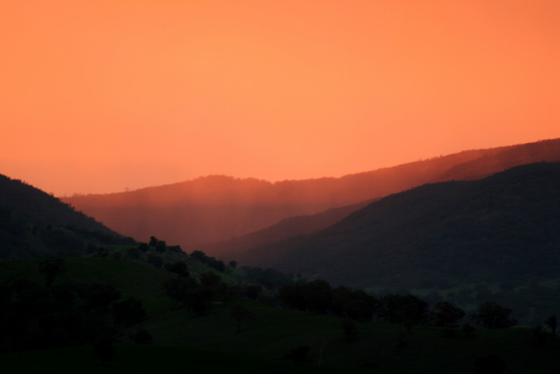 Pink rain in distant valleys, illuminated by the near-horizontal rays of the setting sun; June 2007 long weekend. View towards Reids Flat, New South Wales.
