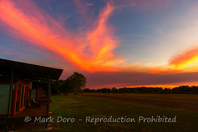 The dry season fires create vivid red sunsets over the lodges at Wildman Wilderness Lodge, Mary River, Northern Territory