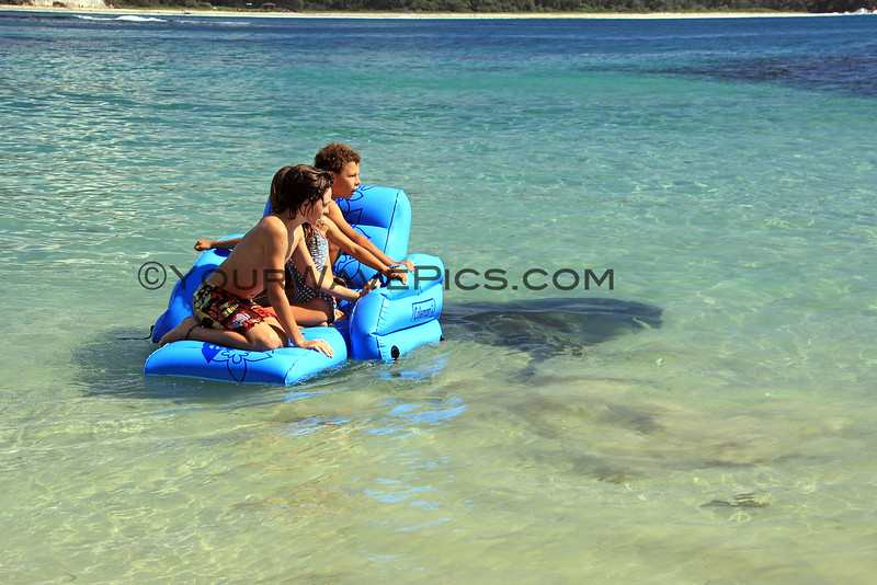 2016-03-24_1401_Bendalong Beach Stingray.JPG<br /> <br /> This little beach is known for giant stingrays that swim near the boat ramp where fishermen throw them scraps of fish.  These kids weren't afraid of the large stingray swimming below their float!