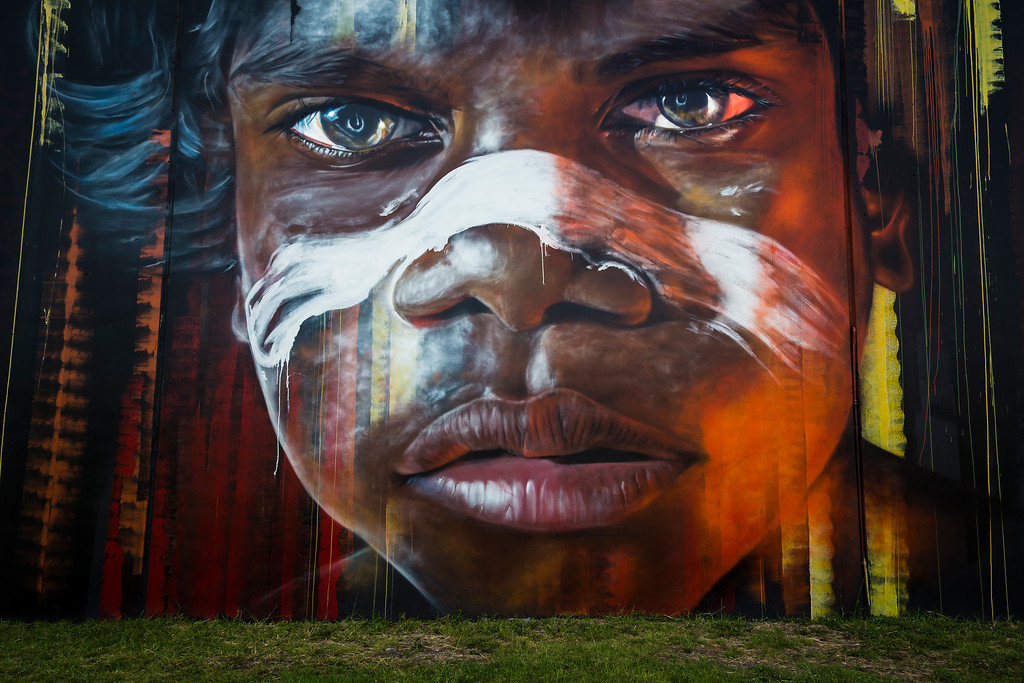 Portrait of a young Aboriginal Boy on the side of a building that overlooks Newcastle Harbour, Australia