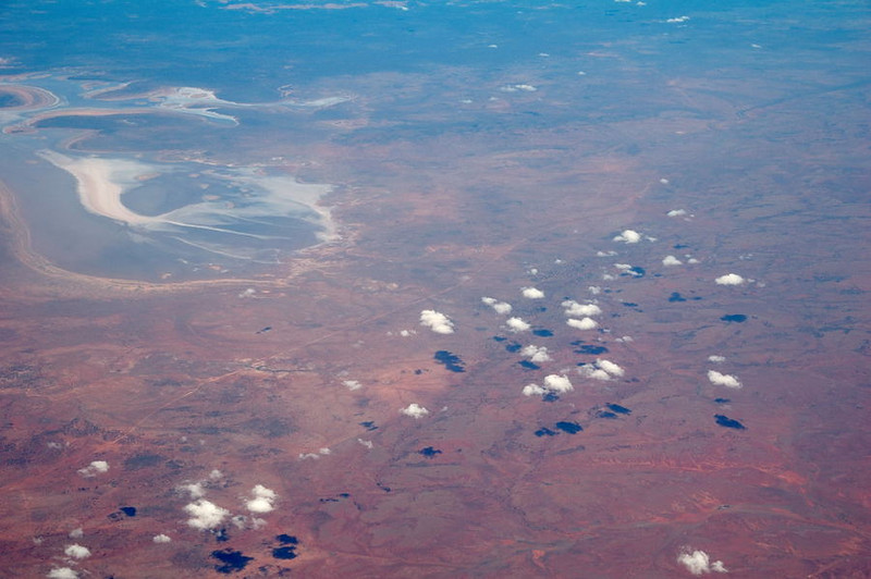 Puffy cumulus clouds cast shadows on the red desert between Adelaide and Alice Springs. Photographed from plane window. A salt lake and a roadway are also visible.<br />    Dec. 20, 2007