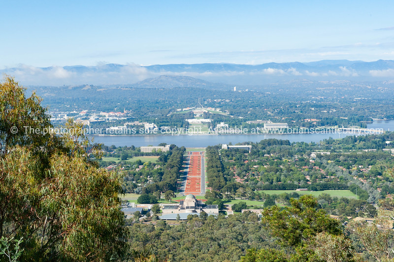 Canberra view from Mount Ainslie aover orange coloured Anzac PArade below to Houses of Parliament