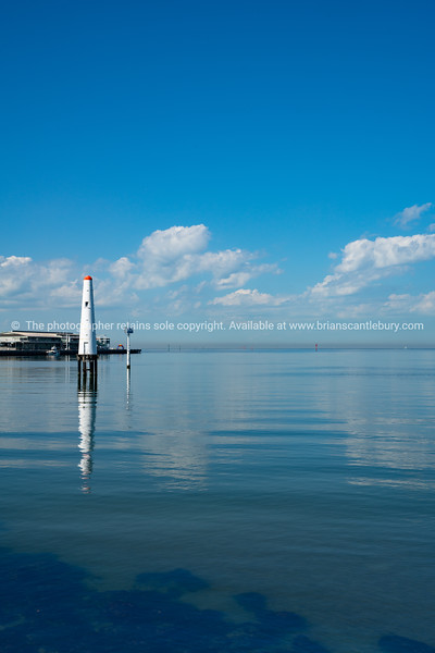 White lighthouse with red top in harbour at Port Philip